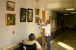 A resident watches as artist Remington Restivo finishes putting up an exhibit of her original oil paintings  at LNRC.